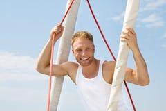 Porträt des blonden hübschen jungen Mannes auf Segelboot. Lizenzfreie Stockfotos
