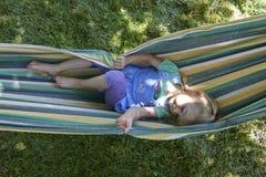 Porträt des blonden Kindermädchens, das auf einer bunten Hängematte sich entspannt Lizenzfreie Stockfotografie