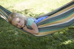 Porträt des blonden Kindermädchens, das, entspannend auf einer bunten Hängematte schläft Stockfoto