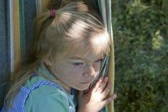 Porträt des blonden Kindermädchens mit den blauen Augen, die auf einer bunten Hängematte sich entspannen Lizenzfreie Stockbilder