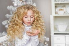 Porträt des blonden kleinen Mädchens betrachtet und brennt einem Konfetti an den Händen im Weihnachtsstudio durch Stockfoto