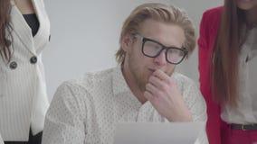 Porträt des blonden Mannes in den Gläsern, die in einem hellen bequemen Büro mit netbook am Tisch sitzen Zwei M?dchen herein stock video