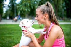 Porträt des blonden weiblichen Spielens mit einem kleinen weißen Hund, bichon lizenzfreie stockbilder