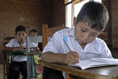 Porträt des bolivianischen Jungenschreibens im Klassenzimmer lizenzfreie stockfotos