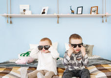 Porträt des Bruders und der Schwester in der Sonnenbrille, die zu Hause auf Bett sitzt Stockfoto