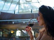 Porträt des brunette Mädchenmodells, das Rotwein von einem Glas trinkt lizenzfreie stockbilder