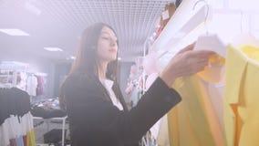 Porträt des brunette Mädchens in einem Bekleidungsgeschäft ein Kleid, Jacke, Anzug kaufend für den Sommer stock video footage
