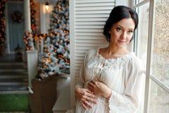 Porträt des Brunettemädchens in Erwartung des Babys in einem Weiß stockfotos