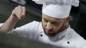 Porträt des Chefs Nahrung an der Küche salzend Chef, der Nahrung in der Zeitlupe kocht stock video footage