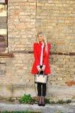 Porträt des dünnen Mädchens stehend nahe einer Wand im roten Kleid mit Han Lizenzfreies Stockfoto