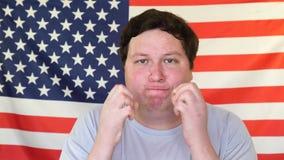 Porträt des dicken Mannes im Druck weil er glaubende Furcht auf dem Hintergrund einer USA-Flagge stock video