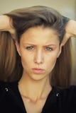 Porträt des die Stirn runzelnden hübschen Mädchens Stockbilder