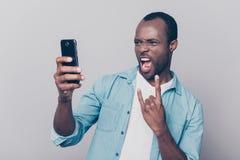 Porträt des dummen, kühlen, einzelnen Kerls, der intelligentes Telefon herein hat Stockfotografie