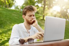 Porträt des durchdachten attraktiven europäischen Mannes mit dem stilvollen Haarschnitt, der im Laptopmonitor gestört wird über n stockfotografie