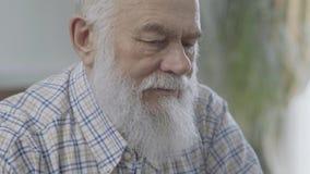 Porträt des durchdachten bärtigen reifen Mannes, der zu Hause nahes oben sitzt Älterer Mann fühlt sich unbequem Alter Mann ha stock video