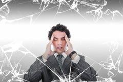 Porträt des durchdachten Geschäftsmannes mit Kopfschmerzen hinter defektem Stockbild