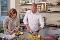 Porträt des Ehemanns und der Frau, die den Käse in der Küche cuting sind Stockbilder