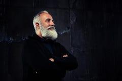 Porträt des einzelnen älteren bärtigen Mannes gegen schwarzen Hintergrund Stockfotos