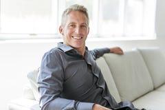 Porträt des einzelnen Mannes 40s, der im Sofa sitzt Stockfotos