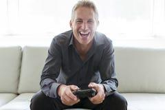 Porträt des einzelnen Mannes 40s, der im Sofaspielvideospiel sitzt Lizenzfreies Stockfoto
