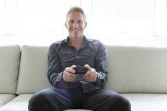 Porträt des einzelnen Mannes 40s, der im Sofaspielvideospiel sitzt Lizenzfreie Stockfotos