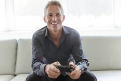 Porträt des einzelnen Mannes 40s, der im Sofaspielvideospiel sitzt Lizenzfreie Stockbilder
