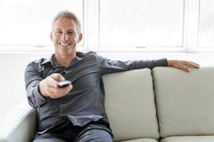 Porträt des einzelnen Mannes 40s, der in Sofafernsehdirektübertragung sitzt Stockfotografie