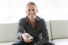 Porträt des einzelnen Mannes 40s, der in Sofafernsehdirektübertragung sitzt Lizenzfreie Stockbilder