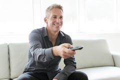 Porträt des einzelnen Mannes 40s, der in Sofafernsehdirektübertragung sitzt Lizenzfreies Stockbild