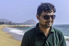 Porträt des eleganten indischen Mannes im formalen T-Shirt und in der Sonnenbrille draußen, Seehintergründe lizenzfreie stockfotografie