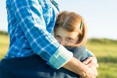 Porträt des Elternteils und des Kindes Mutter umarmt ihre kleine Tochter Naturhintergrund, ländliche Landschaft, grüne Wiese, Nah stockfoto