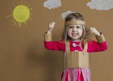 Porträt des emotionalen kleinen Mädchens mit einer Pappklage handmade Hintergrund der gemalten Sonne und der weißen Wolken Stockfoto