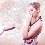 Porträt des Empfangens von Geschenken oder von herrlicher blonder junger Frau der Geschenke, die das glückliche lächelnde Träumen Stockbild