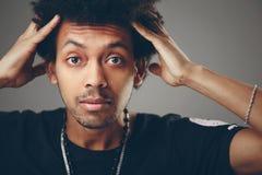 Porträt des entsetzten jungen Afroamerikanermannes, der Kamera betrachtet stockfotos