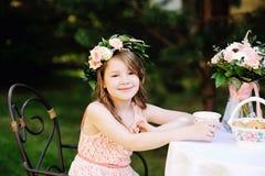 Porträt des entzückenden Kindermädchens am Teetisch Stockbild