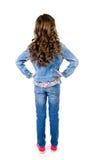 Porträt des entzückenden kleinen Mädchens in den Jeans, die zurück stehen stockbild