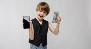 Porträt des entzückenden lustigen aufgeregten kleinen Jungen, der im Studio mit Handy und Geld in seinen Händen auf Grau steht lizenzfreie stockbilder