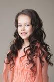 Porträt des entzückenden Mädchens aufwerfend im korallenroten Kleid Stockfotos