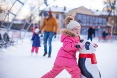 Porträt des entzückenden Mädchens eislaufend auf die Eisbahn Lizenzfreie Stockfotos