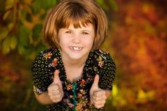 Porträt des entzückenden Mädchens mit Blume in den Haaren, Daumen zeigend lizenzfreies stockbild