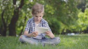 Porträt des entzückenden netten Jungen im karierten Hemd, welches die Blätter Papier im Park betrachtet Sommerzeitfreizeitfreien stock video