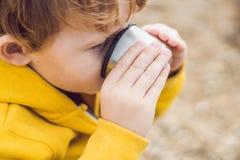 Porträt des entzückenden netten stillstehenden und trinkenden Tees des Jungen von einem Th Lizenzfreies Stockfoto