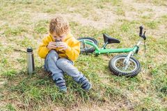 Porträt des entzückenden netten stillstehenden und trinkenden Tees des Jungen von einem Th Stockbild
