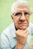 Porträt des ernsten alten Mannes, der Kamera mit den Händen auf Kinn betrachtet Lizenzfreies Stockbild
