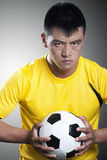 Porträt des ernsten Fußballspielers, der einen Fußball hält stockbild