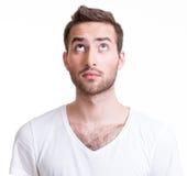 Porträt des ernsten hübschen jungen Mannes, der oben schaut. Stockbild