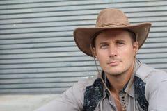 Porträt des ernsten jungen Cowboys mit dem Hut lokalisiert auf strukturiertem grauem Hintergrund mit Kopienraum Stockbild