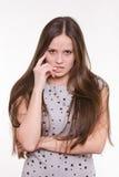 Porträt des ernsten jungen Mädchens mit der Hand nahe Gesicht Stockfotografie