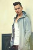 Porträt des ernsten jungen Mannes, der an der Wand sich lehnt Modefrisur Lizenzfreies Stockfoto