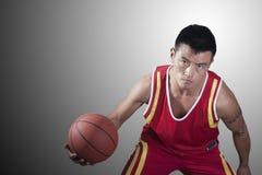 Porträt des ernsten jungen Mannes, der einen Basketball hält stockfotografie